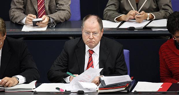 Der analoge Typ: Andere greifen zum Smartphone, Peer Steinbrück macht sich Notizen. Foto: Picture Alliance