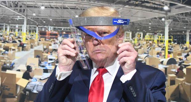 """Bei der Besichtigung der Ford-Fabrik im Mai in Ypsilanti hält US-Präsident Donald Trump ein Gesichtsvisier hoch. Mundschutz trug Trump trotz Aufforderung nicht. Er wolle der Presse keine """"Freude"""" machen. (c) Daniel Mears/Detroit News/TNS via ZUMA Wire"""