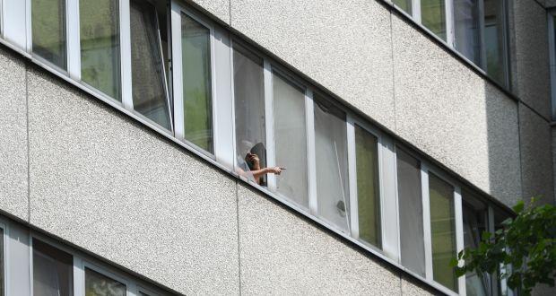 Ein Mann steht am Fenster einer Flüchtlingsunterkunft im Frankfurter Stadtteil Bockenheim. In der Gemeinschaftsunterkunft sind im Mai 65 Bewohner sowie zwei Mitarbeiterinnen des Deutschen Roten Kreuzes (DRK) positiv auf Covid-19 getestet worden. (c) dpa/Arne Dedert